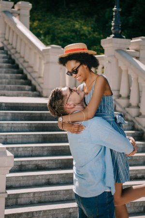 smiling young man holding african american girlfriend near stairs in park