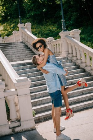 young man holding smiling girlfriend near stairs park