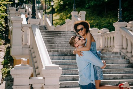 happy young man holding african american girlfriend near stairs in park
