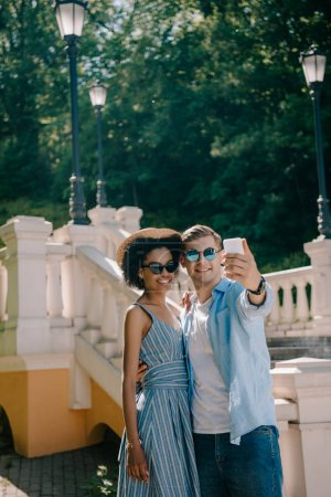 young interracial couple in sunglasses taking selfie on smartphone in park