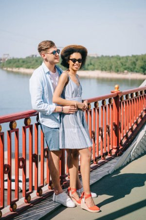 Photo for Multiethnic stylish couple in sunglasses standing on bridge over river - Royalty Free Image