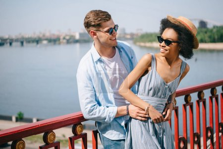 stylish smiling multiethnic couple in sunglasses standing on bridge over river