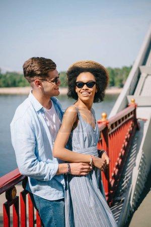 Photo pour Jeune homme élégant en embrassant afrifcan amie américaine sur pont de soleil - image libre de droit