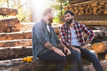 two smiling bearded lumberjacks talking to each other at sawmill