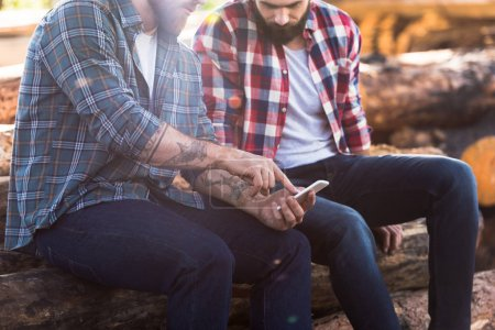 cropped shot of bearded lumberjack pointing by finger on smartphone screen to partner