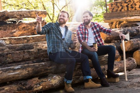smiling lumberjack with coffee cup pointing by finger to partner with axe sitting on logs at sawmill