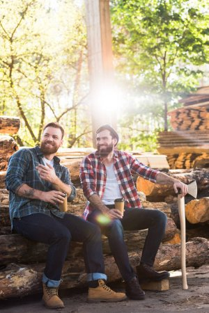 lumberjack with coffee cup pointing by finger to partner with axe sitting on logs at sawmill