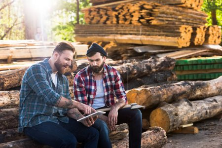 bearded lumberjacks sitting on logs with axe and digital tablet at sawmill