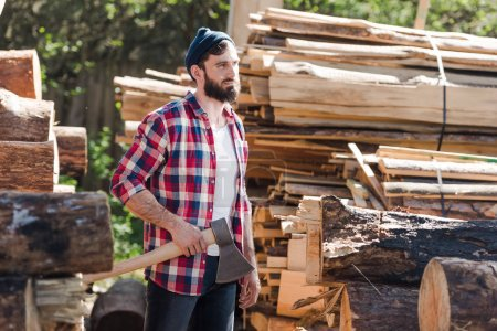 bearded lumberjack in checkered shirt standing with axe at sawmill