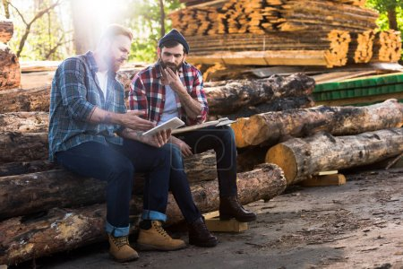 two lumberjacks sitting on logs with axe and using digital tablet at sawmill