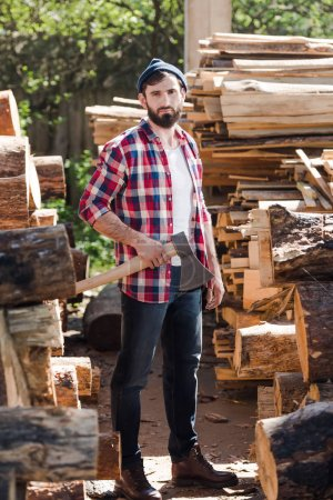 lumberjack in checkered shirt standing with axe between logs at sawmill