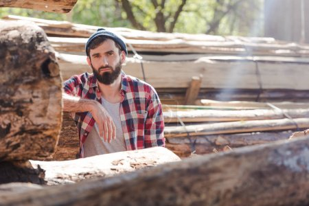 bearded lumberjack in checkered shirt standing at sawmill