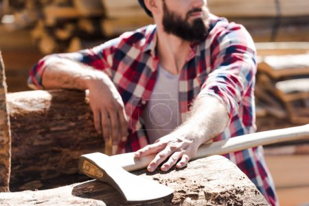cropped image of bearded lumberjack in checkered shirt with axe at sawmill