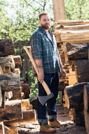 Photo for Bearded lumberjack  in checkered shirt standing with axe at sawmill - Royalty Free Image