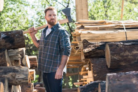 lumberjack in checkered shirt holding axe on shoulder between logs at sawmill