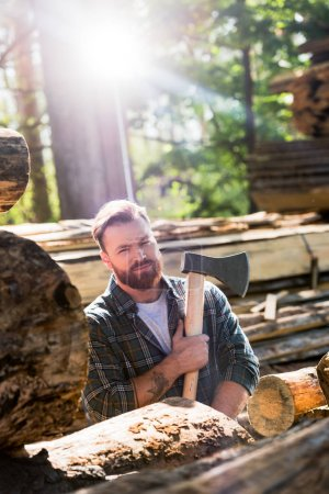 lumberjack in checkered shirt with tattooed hand holding axe at sawmill