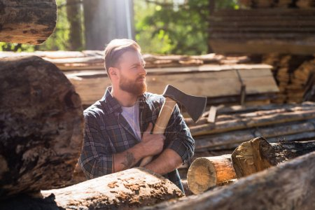 side view of lumberjack in checkered shirt with tattooed hand holding axe at sawmill