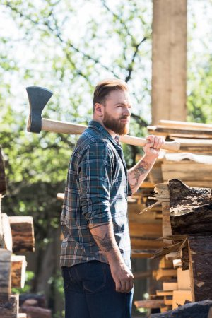 bearded lumberjack in checkered shirt with tattooed hand holding axe on shoulder at sawmill