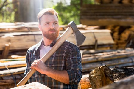 lumberjack in checkered shirt holding axe on shoulder at sawmill