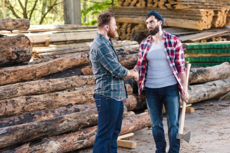 lumberjack with holding axe and shaking hands with partner at sawmill