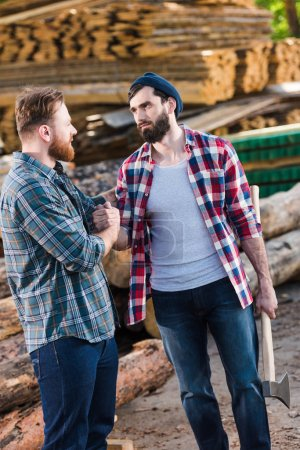 bearded lumberjack in checkered shirt holding axe and shaking hands with partner at sawmill
