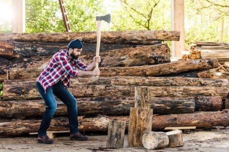 side view of bearded lumberjack in checkered shirt chopping log at sawmill