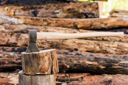 side view of sticking axe in log at sawmill