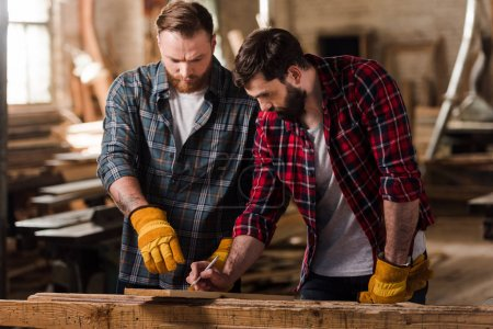 bearded carpenter in protective gloves pointing on wooden plank to partner with pen in hand