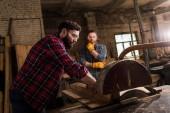 charpentier dans googles de sécurité à l'aide de la machine scie et partenaire debout derrière à la scierie