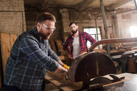 bearded carpenter in safety googles using machine saw and partner with crossed arms standing behind at sawmill
