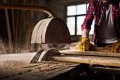 image recadrée de charpentier dans les gants de protection à l'aide de machine scie à la scierie