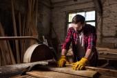 Barbu de travailleur dans googles protection et des gants à l'aide de machine scie à la scierie