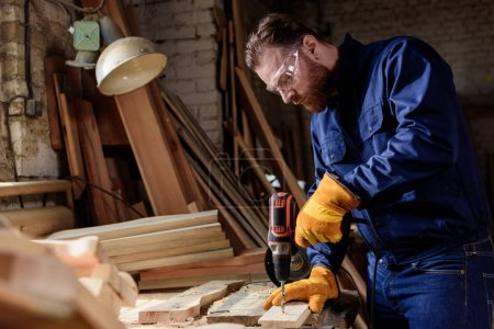 bearded carpenter in protective gloves and googles using electric drill at sawmill