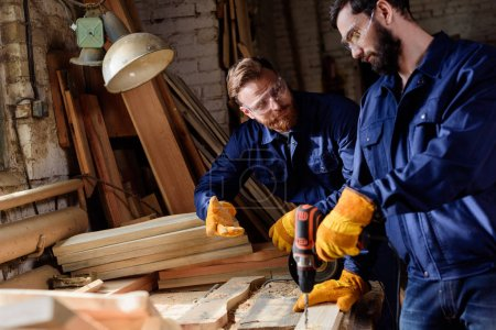 bearded craftsman pointing to partner in protective gloves and googles working with electric drill at sawmill