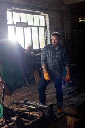 Photo pour Artisan barbu dans les gants de protection debout près de la machine à la scierie - image libre de droit
