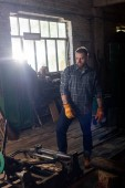 bearded craftsman in protective gloves standing near machine at sawmill