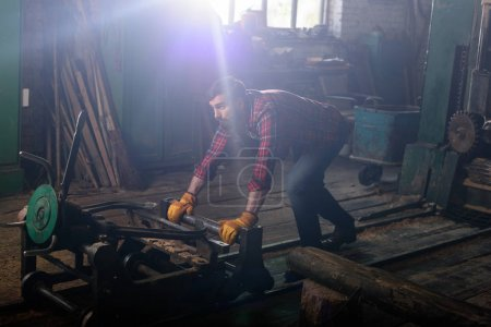 bearded worker in protective gloves pushing machine at sawmill