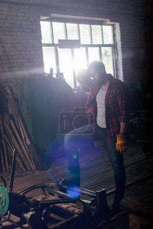 Foto de Trabajador barbudo en guantes limpiar la frente y de pie junto a la máquina en el aserradero - Imagen libre de derechos