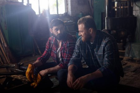 two bearded workers sitting and talking to each other at sawmill