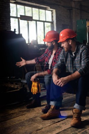 worker in protective helmet pointing on machine to colleague at sawmill