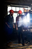 two bearded workers in protective helmets using machine tool at sawmill