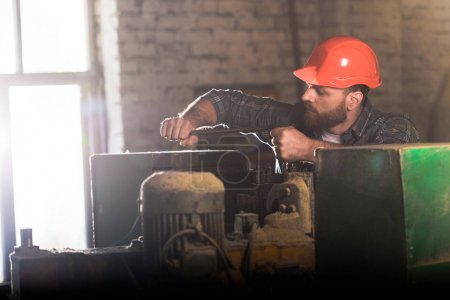 bearded worker in protective helmet repairing machine tool at sawmill