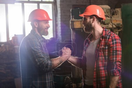 side view of bearded carpenters in protective helmets shaking hands at sawmill