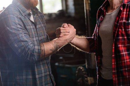 Photo pour Image recadrée de charpentier avec main tatouée serrant la main du partenaire à la scierie - image libre de droit