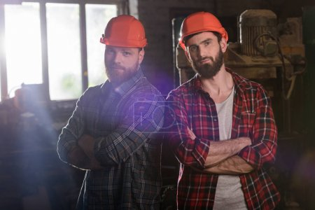two bearded carpenters with crossed hands in protective helmets standing at sawmill