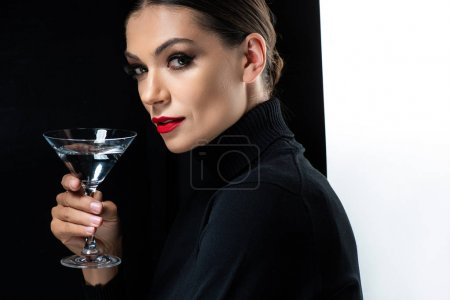 Photo for Beautiful elegant woman with red lips holding martini isolated on white and black - Royalty Free Image