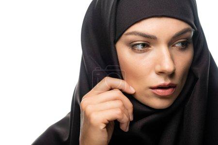 Photo pour Belle jeune femme musulmane touchant hijab et regardant loin isolé sur blanc - image libre de droit