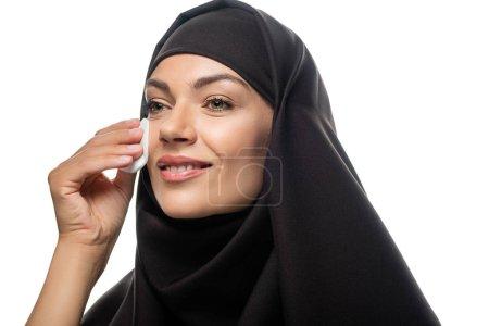 Photo pour Jeune femme musulmane souriante en hijab essuyant le visage avec du coton isolé sur blanc - image libre de droit