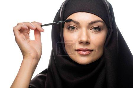 Photo pour Jeune musulmane en hijab appliquant du mascara sur les cils isolés sur du blanc - image libre de droit
