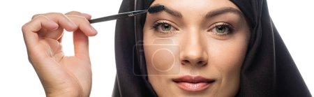 Photo pour Jeune musulmane en hijab appliquant du mascara sur des cils isolés sur une pellicule blanche panoramique - image libre de droit
